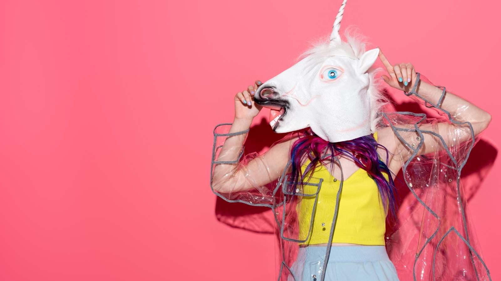 person in a unicorn mask against pink background